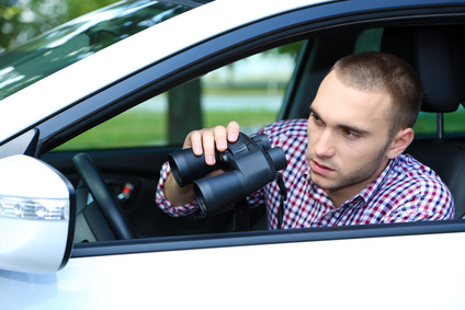 Man in car with binoculars